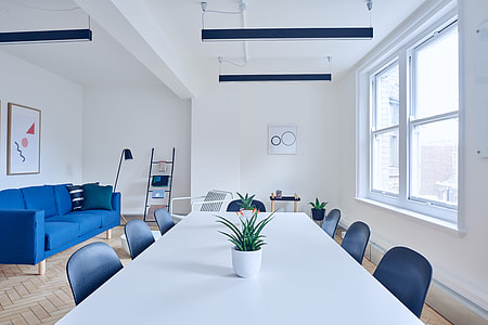 empty room with white wooden long table near blue suede 3-seat sofa