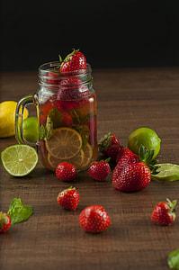 sliced lemon and strawberries on clear mason jar