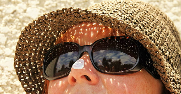 woman wearing black sunglasses and brown hat