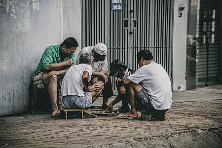three men watching two men playing board game on street during daytime