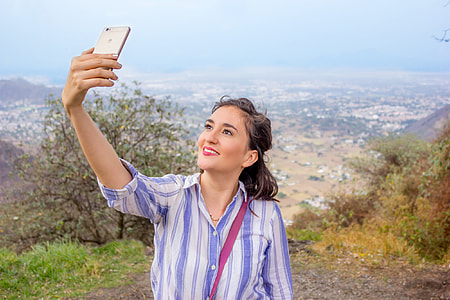 woman in blue and white striped button-up shirt during daytime