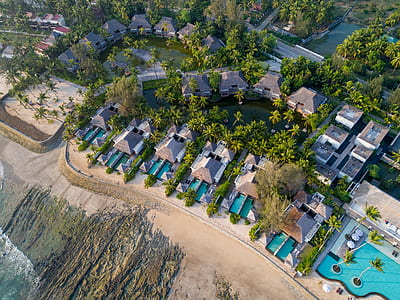 bird's eye view of resort houses and swimming pools surrounded by trees during daytime
