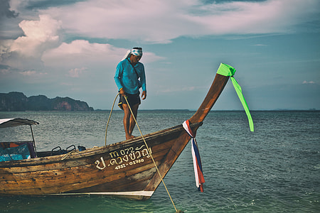 A man secures a longtail boat with rope in the Krabi district of Thailand