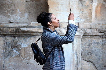 woman holding her phone near brown wall