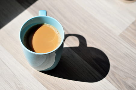 teal ceramic mug filled of coffee