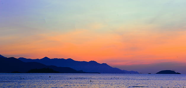 Silhouette of Mountain Beside Ocean during Orange Sunset