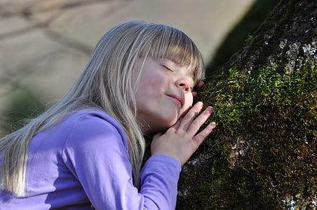 girl in purple long-sleeved shirt sleeping on black and green tree body during daytime