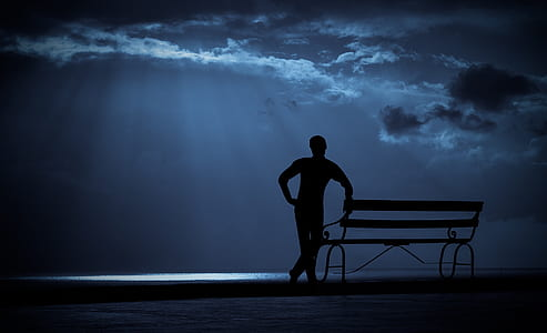 silhouette of man besides bench under cloudy sky