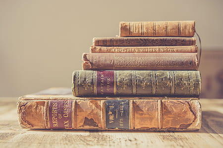 selective focus photography of pile of hardbound books