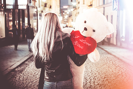 Young Woman Holding Her Big Valentine's Day Gift Teddy Bear