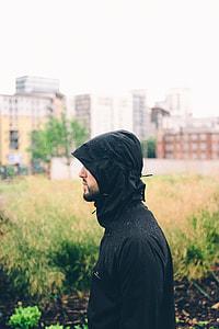 side view of man in black windbreaker jacket