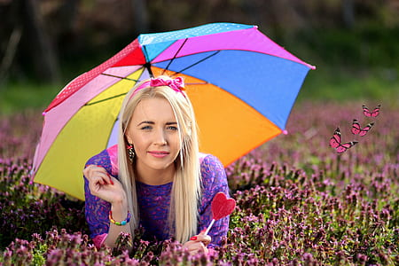 selective focus photography of woman wearing purple dress holding umbrella