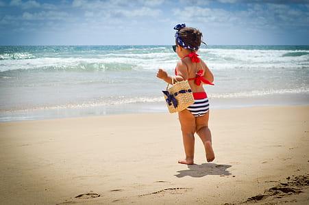toddler girl near body of water during daytime