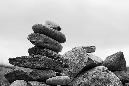 grayscale photo of pile of gray stones