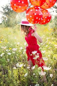 woman holding balloon wearing red sleeveless dress