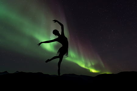 silhouette photography of ballet dancer in northern lights