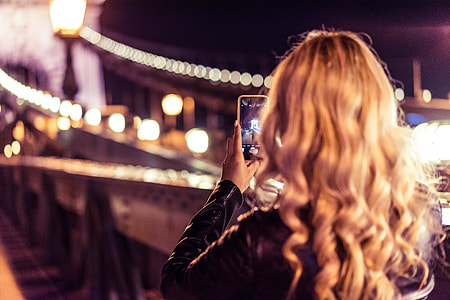 Blonde Woman Taking a Photo of an Old Bridge at Night