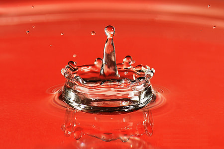 Closeup shot of a water drop splash on red background