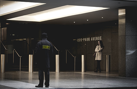 woman and security guard standing inside hall