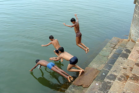 boys diving in water during daytime