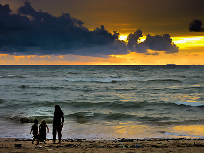 silhouette of woman and two toddlers on seashore