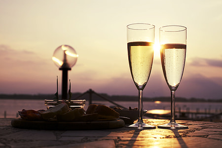 two long-stem wine glasses beside body of water photography