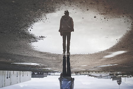 man standing near water with reflection during daytime
