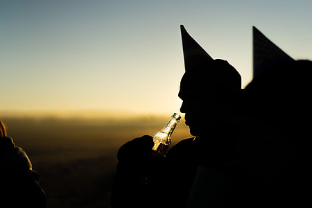silhouette of a person holding beer