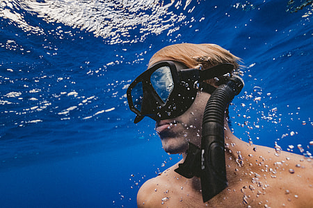 man in black underwater goggles and snorkel in body of water