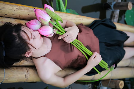 woman holding pink petaled flowers while lying on bamboo