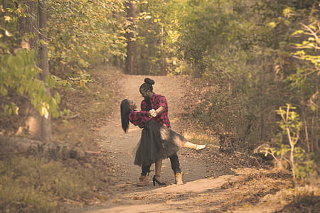 man and woman in the center of forest photography