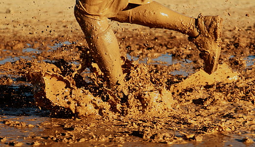 person on mud during daytime