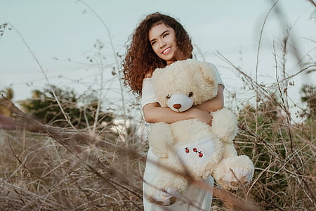 woman carrying yellow and white bear plush toy