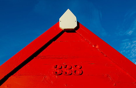 A red coastal hut contrasts against a blue sky