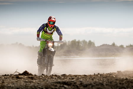 Person In Green Motocross Gear Riding A Dirt Bike