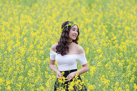 selective focus portrait photograph of woman wearing white off-shoulder dress on a bed of yellow petaled flowers