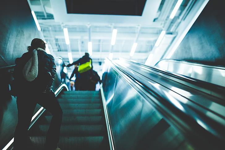 Person Riding on Escalator