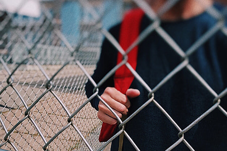 Child by fence in school playground