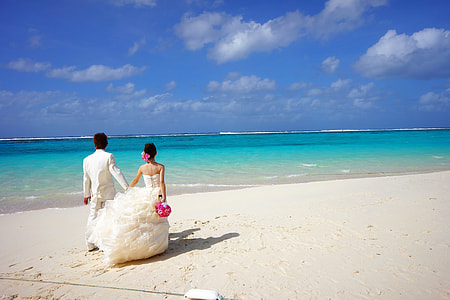 newly wedding couple walks on shoreline during daytime