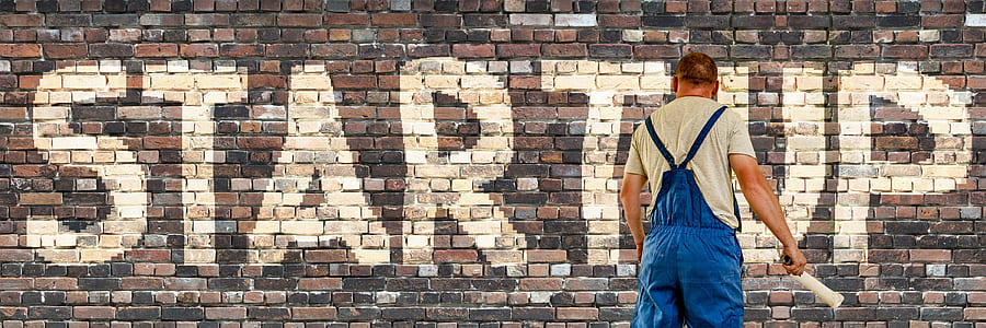 man painting startup text on wall