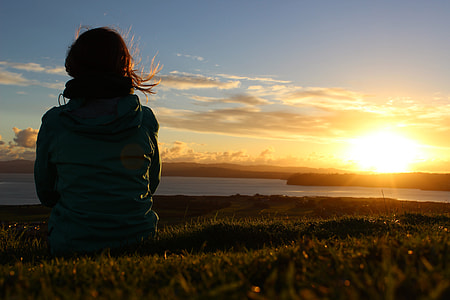 silhouette photography of woman sitting on grass in front of ocean