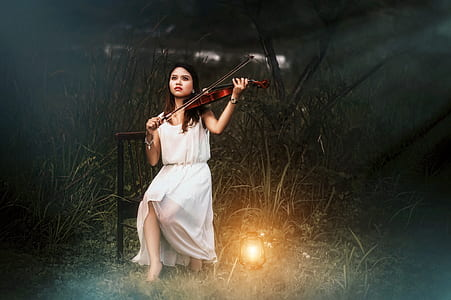 woman in white scoop-neck sleeveless dress holding brown violin