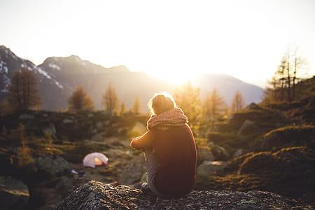 photo of man sitting on stone during daytime