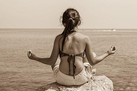 meditating woman sitting on rock