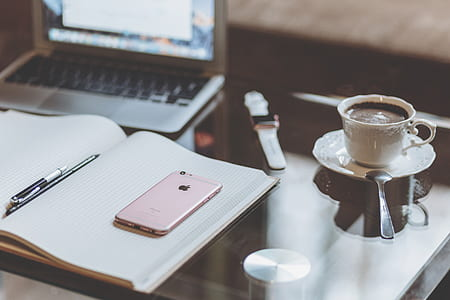 iPhone beside pen and coffee