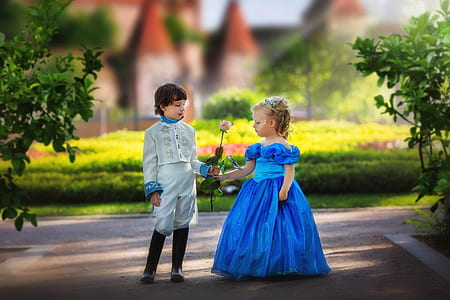 boy in white suit giving flower to a girl in blue gown