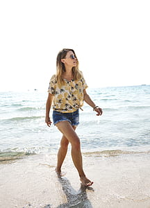 woman wearing beige pineapple print shirt walking on seashore