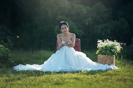 woman in white wedding dress sitting on seat