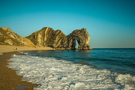large form of rock near seashore at daytime