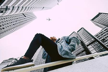 photo of man sitting on baluster